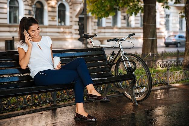 Mooie casual vrouw praten op de mobiele telefoon zittend op de bank met een kopje koffie