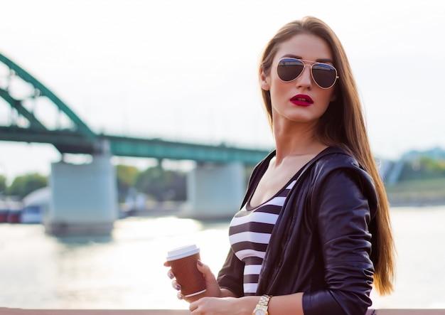 Mooie casual zakenvrouw, meisje met koffie bij de zonsondergang van de rivier.