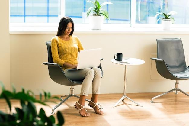 Mooie casual zakenvrouw zittend op een bureaustoel en met behulp van laptop op kantoor