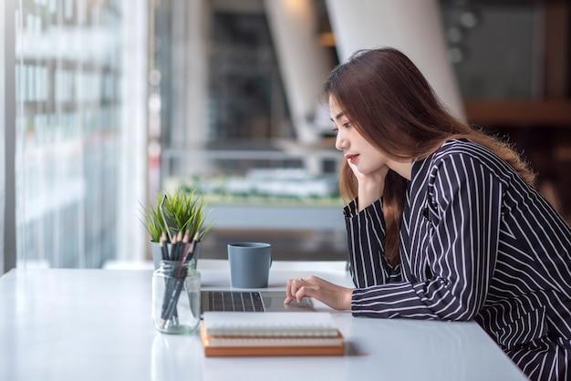 Mooie, charmante aziatische bedrijfsvrouw die met een laptop computer aan een modern bureau werkt