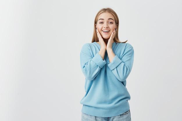 Mooie charmante blonde blanke meisje draagt blauwe trui en spijkerbroek wijd open mond, zegt wow, opgewonden verbaasd blik, hand in hand op haar gezicht, blij met onverwacht cadeau