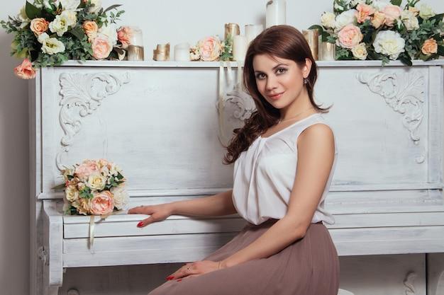 Mooie charmante brunette binnenshuis, oude piano