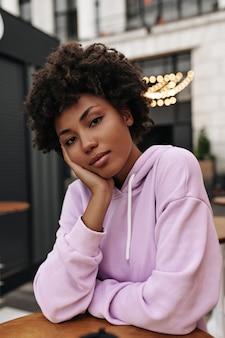 Mooie charmante brunette krullende vrouw in stijlvolle paarse hoodie leunt op houten tafel en kijkt naar de camera buiten