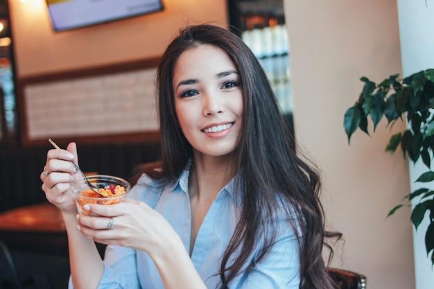 Mooie charmante brunette lachende aziatische meisje heeft ontbijt met chia pudding in café