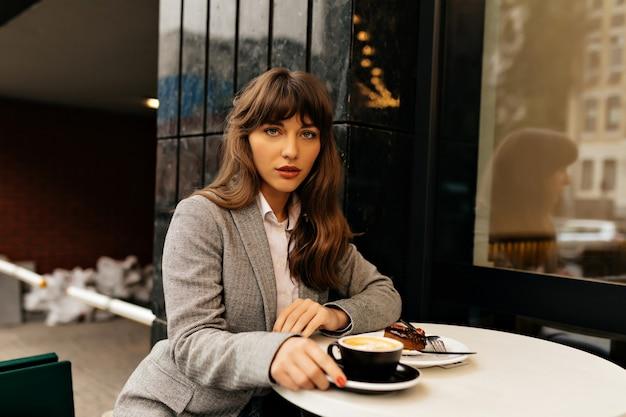 Mooie charmante dame in grijze jas met lang golvend haar zittend op stadscafetaria heeft koffiepauze