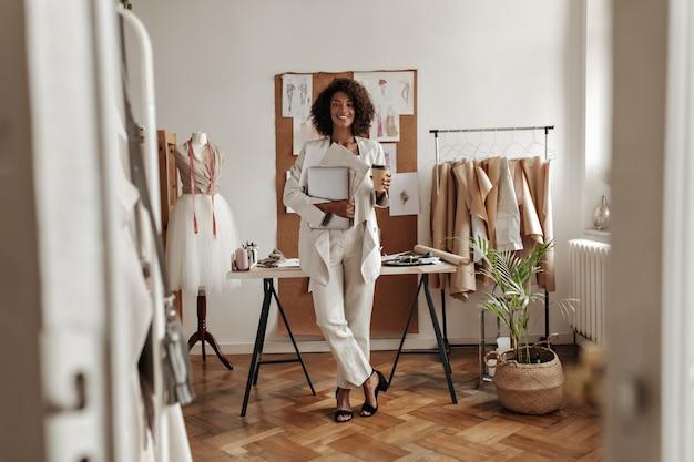 Mooie charmante dame met donkere huidskleur in witte jas en broek lacht, houdt laptop en koffiekop vast