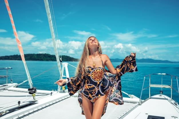 Mooie, charmante glimlachende, blonde met lang haar, in een gekleurd zwempak met een strandjas, staand staand, op het dek van het jacht met haar ogen dicht. zee-plezier. natuur. geluk.