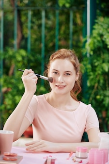 Mooie charmante jonge vrouw die gezichtspoeder op haar neus aanbrengt met een pluizige synthetische borstel