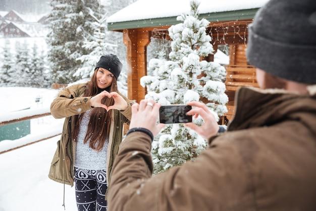 Mooie charmante jonge vrouw die hart met handen toont en poseert voor haar vriend die foto's van haar maakt met mobiele telefoon