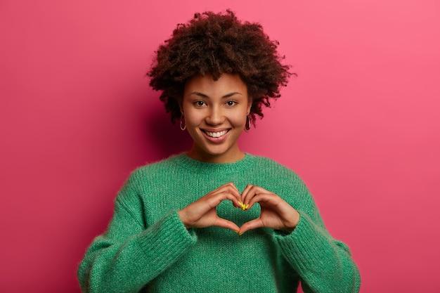 Mooie charmante vrouw geeft vorm aan hartgebaar, laat zien wat vriendje voor haar betekent, drukt genegenheid en liefde uit, lacht aangenaam, draagt een groene trui, geïsoleerd over een roze muur. lichaamstaal concept