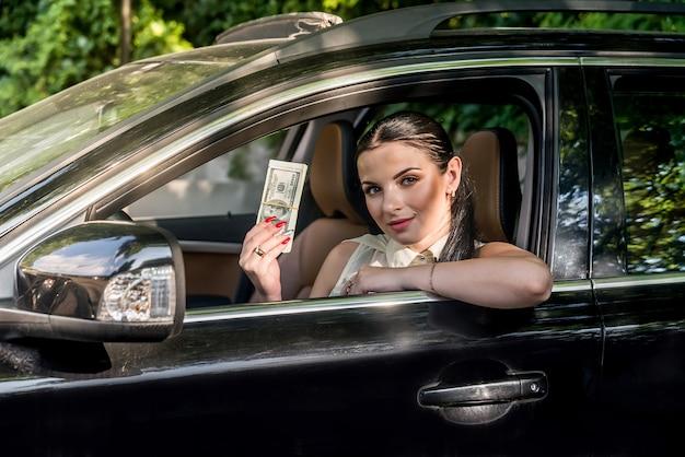 Mooie chauffeur die een stapel dollar aanbiedt, zittend in de auto