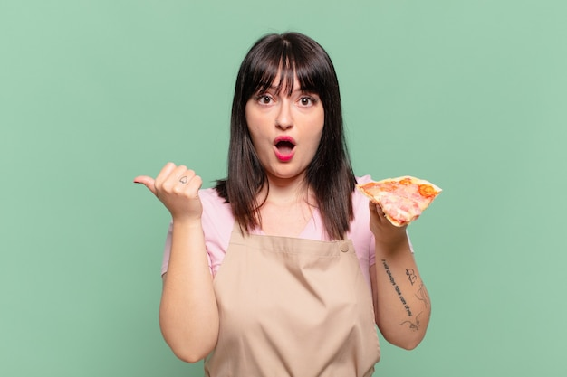 Mooie chef-kok vrouw bang uitdrukking en met een pizza