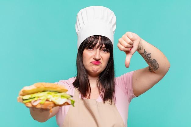 Mooie chef-kok vrouw droevige uitdrukking en met een sandwich