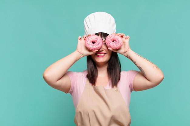 Mooie chef-kok vrouw gelukkige uitdrukking en donuts te houden