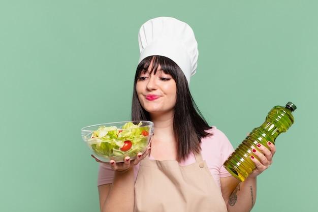 Mooie chef-kok vrouw gelukkige uitdrukking en met een salade