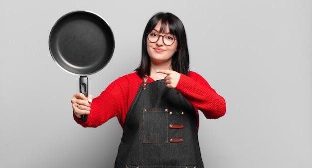 Mooie chef-kok vrouw koken met een pan