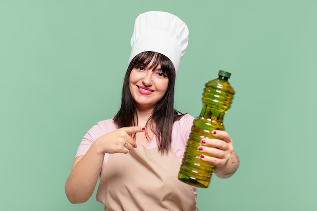 Mooie chef-kokvrouw die een olijfoliefles wijst of toont en vasthoudt