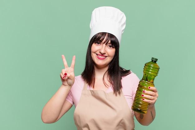 Mooie chef-kokvrouw die succesvol een overwinning viert en een olijfoliefles houdt