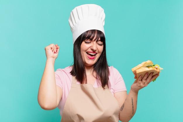 Mooie chef-kokvrouw die succesvol een overwinning viert en een sandwich houdt