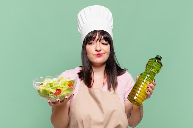 Mooie chef-kokvrouw die twijfelt of een onzekere uitdrukking heeft en een salade vasthoudt