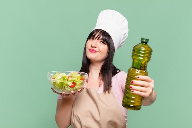 Mooie chef-kokvrouw die uitdrukking denkt en een salade houdt Premium Foto