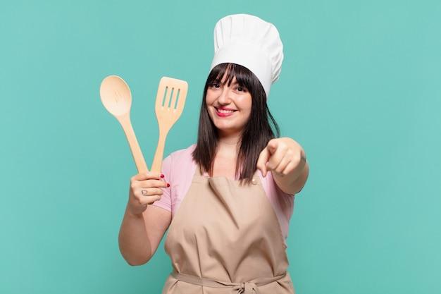 Mooie chef-kokvrouw die wijst of laat zien