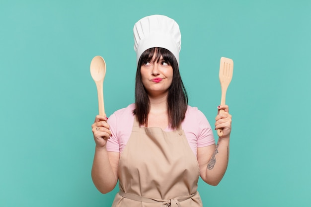 Mooie chef-kokvrouw twijfelende of onzekere uitdrukking