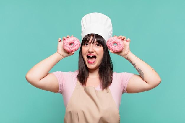 Mooie chef-kokvrouw verraste uitdrukking en houdt donuts