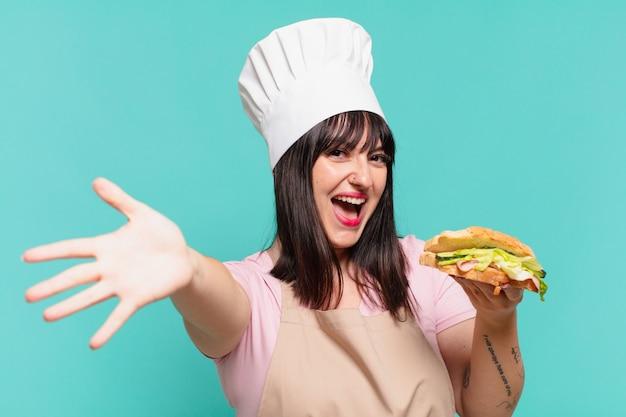 Mooie chef-kokvrouw verraste uitdrukking en houdt een sandwich vast