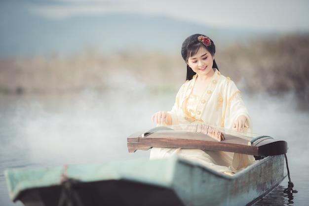 Mooie chinese vrouw die en het traditionele chinese muziekinstrument boa zit speelt