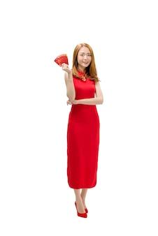 Mooie chinese vrouw in traditionele kleding die rode enveloppen houdt