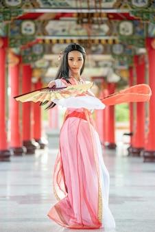Mooie chinese vrouw met een traditioneel kostuum met slag in haar handen. Premium Foto