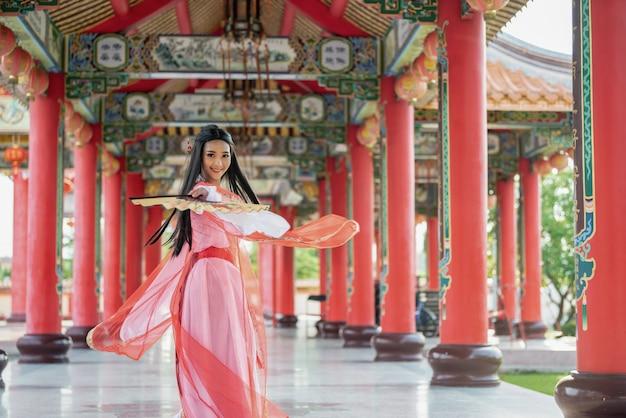 Mooie chinese vrouw met een traditioneel kostuum met slag in haar handen.