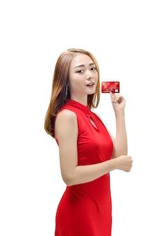 Mooie chinese vrouw met traditionele kleding die haar creditcard toont