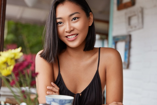 Mooie chinese vrouw portret met kortgeknipt kapsel, poses in gezellige kamer Gratis Foto