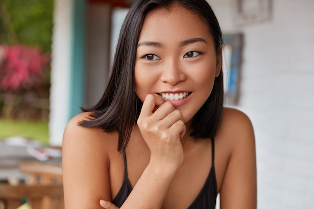 Mooie chinese vrouw portret met kortgeknipt kapsel, poses in gezellige kamer