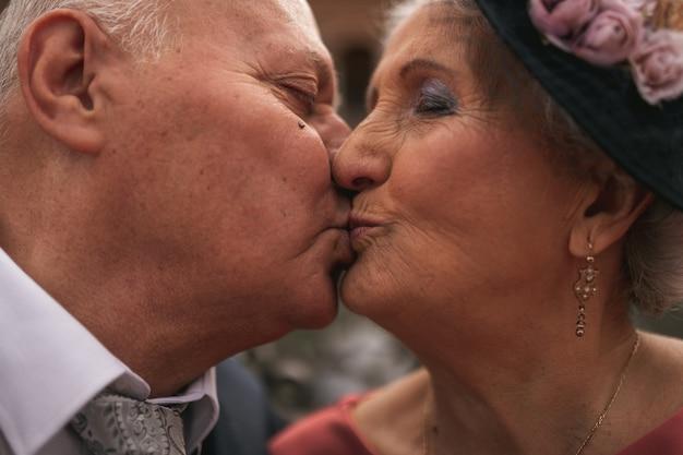Mooie close up van een ouder echtpaar in de dag van hun gouden bruiloft kussen elkaar in de mond. oude mensen blij.