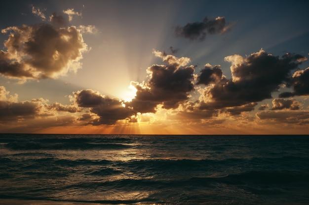 Mooie cloudscape over de dramatische zonsopgang van de zee die op het strand is ontsproten