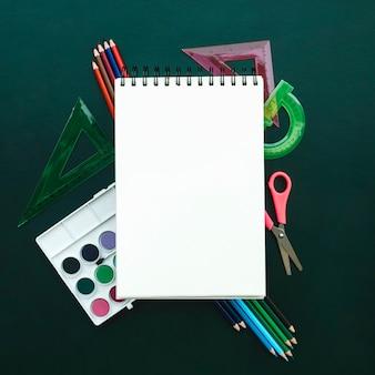 Mooie compositie met een notebook met aquarellen liniaal, potlood op groen bord voor terug naar school