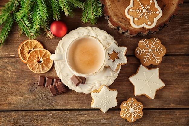 Mooie compositie met kerstkoekjes en kopje koffie op tafel