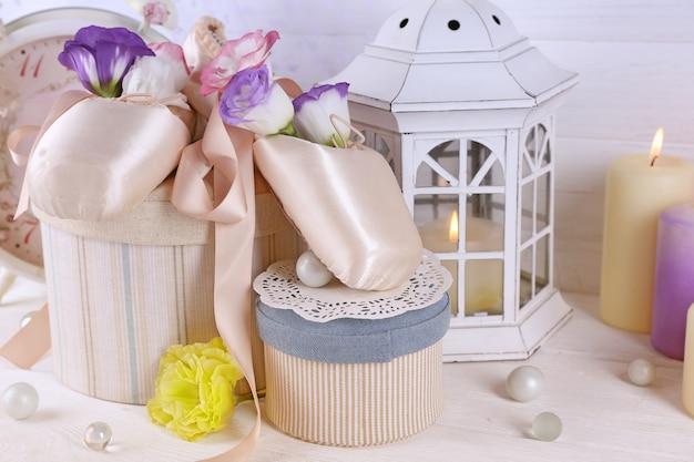 Mooie compositie van balletschoenen, kaarsen, bloemen en kisten, close-up