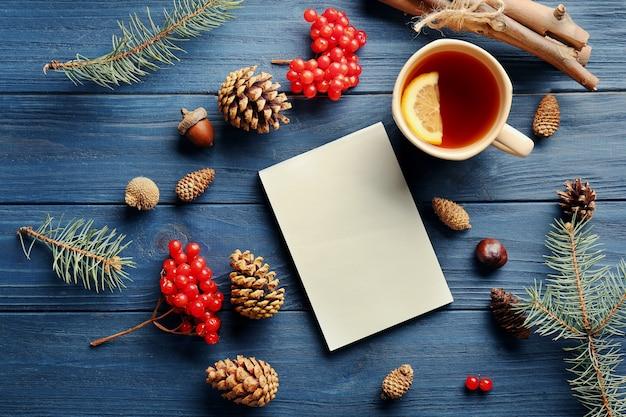 Mooie compositie van notitieboekje, kopje thee, viburnum en kegels op blauwe houten tafel