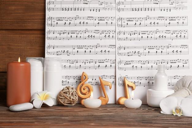 Mooie compositie van spa-accessoires en muzieknoten op bruin houten oppervlak