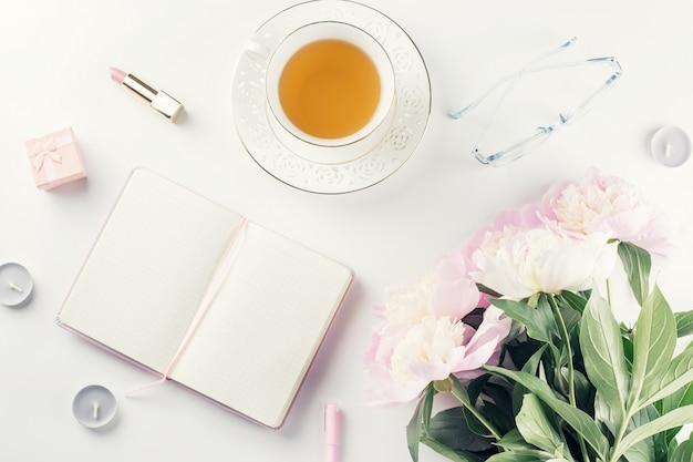 Mooie cosmetica en bloemen plat lag met notitieboek, kruidenthee op pastel achtergrond.