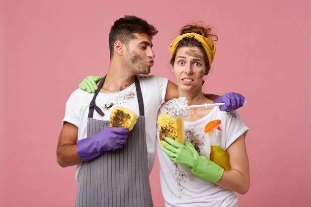 Mooie coupe: knappe man die haar vrouw omhelst en haar wil kussen en haar helpt bij het schoonmaken van hun huis
