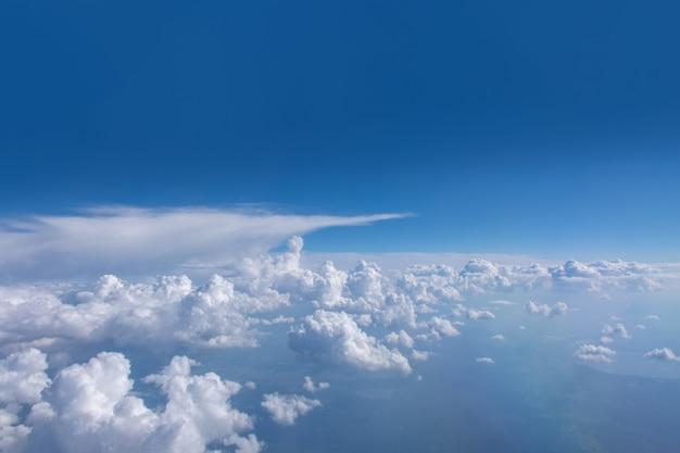 Mooie cumulus pluizige witte wolken op een blauwe hemel met felle zon. perfecte abstracte hemelachtergrond, behang, lay-out. zonsopgang boven wolken vanuit vliegtuigraam