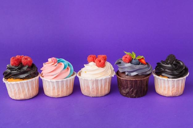 Mooie cupcake tegen verzadigde donkerpaars