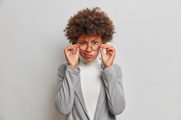 Mooie curly haired vrouwelijke leraar kijkt aandachtig door een bril