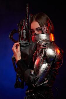 Mooie cybervrouw die geweer houdt en haar gezicht op donkere achtergrond verbergt. gekleed in zwarte jas martial vrouw in cyberpunk stijl kijkt naar de camera.