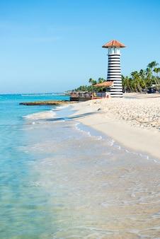 Mooie dag op zee. wit zand, tropische palmbomen en vuurtoren aan zandstrand